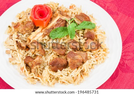 Mutton Biryani Closeup - Closeup view from the top of delicious mutton (lamb) biryani garnished with tomato peel and mint. - stock photo