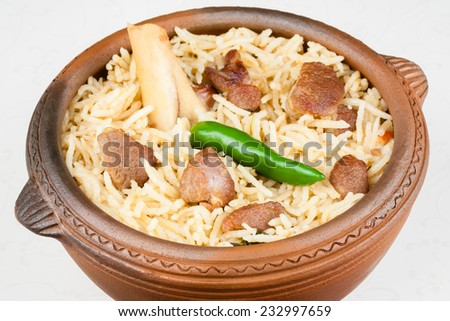 Mutton Biryani Closeup - Closeup view from the top of delicious mutton (lamb) biryani with garnish. Served in an earthenware bowl. - stock photo