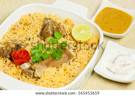 Mutton Biryani with Condiments - Closeup view of delicious mutton (lamb) biryani garnished with tomato peel, cilantro and lemon. Served with its condiments onion salad (raita) and vegetable curry. - stock photo