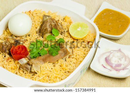 Mutton Biryani with Egg - Closeup view of delicious mutton (lamb) biryani garnished with tomato peel, cilantro and lemon. It is served with hard boiled egg, onion salad (raita) and vegetable curry. - stock photo