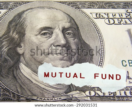 Mutual fund text on a paper scrap over one hundred dollar on foreground. - stock photo