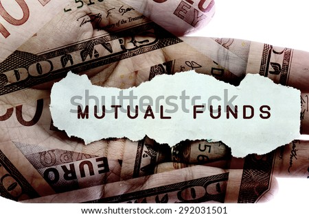 Mutual funds text on a paper scrap. World currency in the background - stock photo
