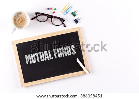 MUTUAL FUNDS word on Chalkboard with Coffee Cup, view from above - stock photo