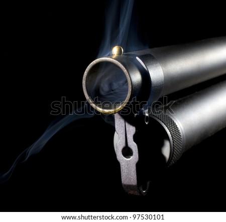 Muzzle of a twelve gauge shotgun that has smoking coming out - stock photo