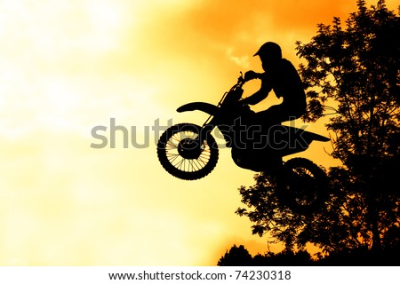 MX Rider silhouette on fire sky - stock photo