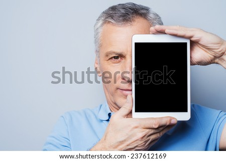 My assistant  in any cases. Confident senior man holding his digital tablet in front of his face and smiling while standing against grey background - stock photo