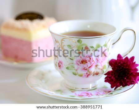 My beautiful cup of tea violet flower and soft cake in soft focus. - stock photo