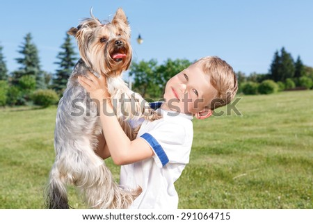 My best friend. Nice little boy keeping his arms up and holding dog in hands while having great time with it. - stock photo
