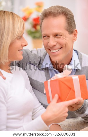 My best wishes. Cheerful pleasant smiling adult couple holding present and resting on the couch while feeling overwhelmed with emotions  - stock photo