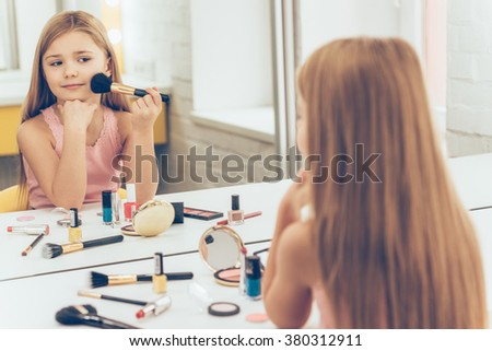 My cheekbones on point today! Cheerful little girl applying make-up and looking at her reflection in mirror while sitting at the dressing table - stock photo
