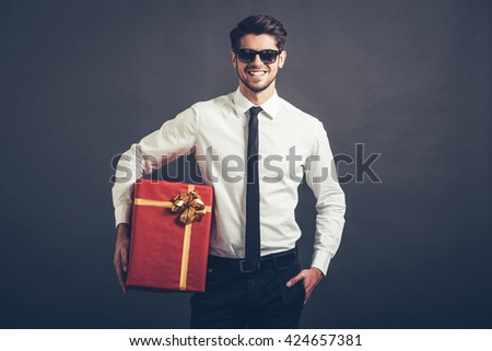 My congratulations! Cheerful handsome well-dressed young man in sunglasses holding gift box and looking at camera with smile while standing against grey background - stock photo