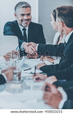 My congratulations! Confident mature man in formalwear shaking hand to one of his colleagues and smiling while sitting at the table together - stock photo