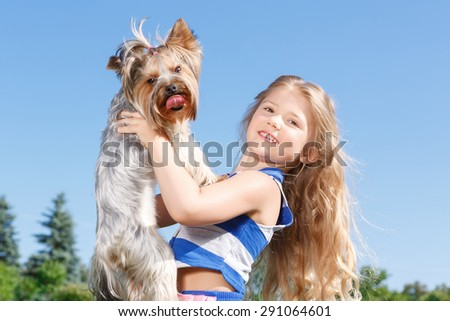 My darling. Positive pretty girl keeping her hands up and holding dog in them while smiling. - stock photo