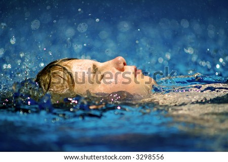 My daughter in the pool while it was raining. - stock photo