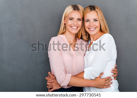 My daughter is my treasure. Smiling mother and her daughter embracing and looking at camera while standing against grey background - stock photo