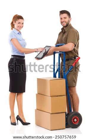My delivery has just arrived. Smiling office female worker receives delivery from messenger and tapping at digital tablet. Full length studio shot isolated on white. - stock photo