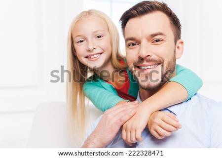 My father is the best! Cute little girl embracing her father and smiling while sitting on the couch at home  - stock photo