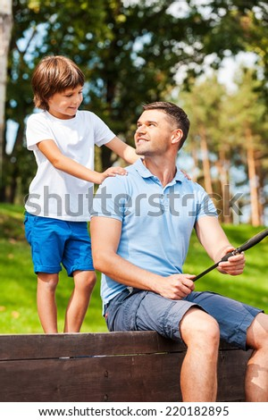 My father is the best! Happy father and son fishing together while sitting on quayside - stock photo