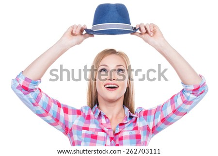 My favorite hat! Beautiful young woman in funky wear holding her hat upon head and looking at it with smile while standing against white background - stock photo