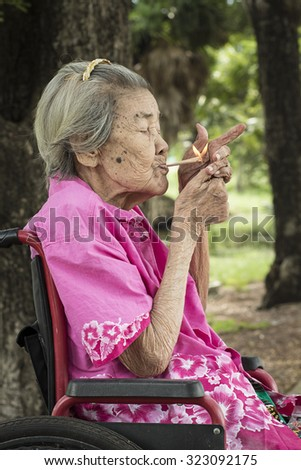 My grandmother Happy even at the age of eighty-two years . Patients with paralysis. Started smoking at the age of fourteen years . Approximately during World War 2 . Grandma happy every day . - stock photo