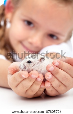 My little pal - girl holding her hamster in palms - stock photo