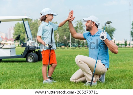 My little winner! Cheerful young man and his son giving high-five to each other while standing on the golf course - stock photo
