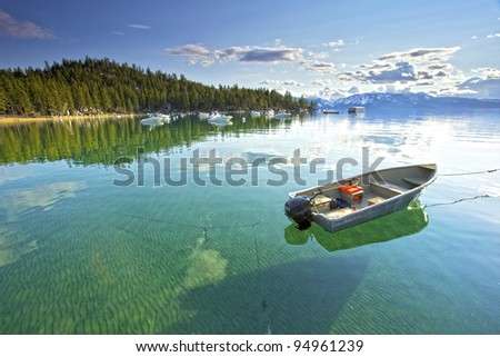 My lonely little fishing  boat setting on the Calm clear water in lake Tahoe, with Trees and Mountains in the background - stock photo