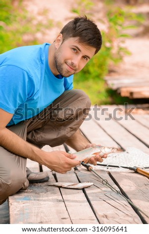 My lucky catch. Pleasant delighted upbeat man holding fish and feeling glad while fishing - stock photo