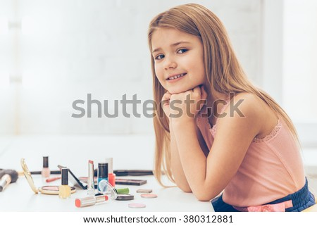My make-up is on point today! Side view of cheerful little girl keeping hands on chin and looking at camerawith smile while sitting at the dressing table - stock photo
