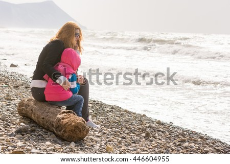 My mother and five year old daughter sitting on the beach, my mother hugged her frozen girl