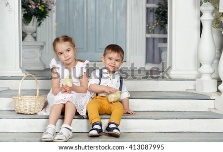 My sister and younger brother sitting on the stairs at home and keep in the hands of chickens and smiling - stock photo