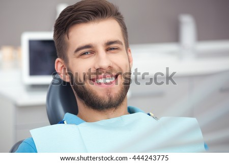 My smile is perfect! Portrait of happy patient in dental chair.