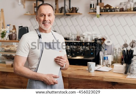 My start up. Happy and confident male cafe worker in apron holding a sheet of white paper while smiling at a camera, standing in a coffeehouse
