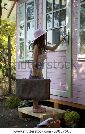 My sweet home. Little girl going back in her wood house for playtime. - stock photo