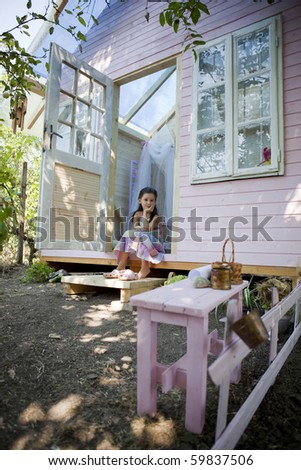 My sweet home. Little girl in her wood house for playtime. - stock photo