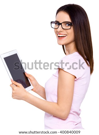 My tablet works for me. Young woman in glasses using electronic tab over white background - stock photo