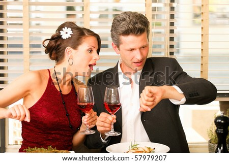 my watch is missing - surprised couple in a restaurant - stock photo