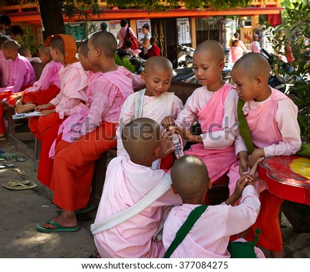 Myanmar , Sagaing, November 2014  School for girlLittle girls-nuns .Buddhist nuns in a break between lessons playing with dolls - stock photo