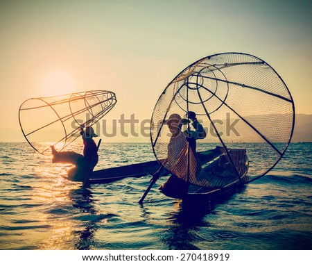 Myanmar travel toursist attraction landmark - two traditional Burmese fishermen at Inle lake, Myanmar on sunrise. Vintage filtered retro effect hipster style image - stock photo
