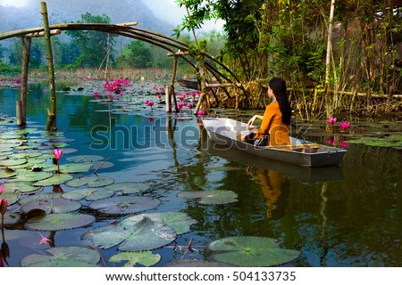MYDUC, VIETNAM - OCTOBER 09, 2016: girl in traditional costume rowing boat in fog in the flooded forest in MYDUC, VIETNAM. MYDUC is a district about 60 km from Hanoi.