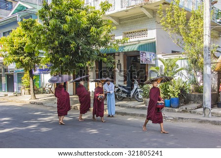 MYEIK, MYANMAR - FEBRUARY 20, 2015: A buddhist believer is offering food to the monks in the streets of Myeik in the south of Myanmar - stock photo