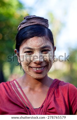 MYITKYINA, MYANMAR - JANUARY 4: Smiling Burmese girl with thanaka paste on the face poses for a photo on January 4, 2012 in Myitkyina, Myanmar