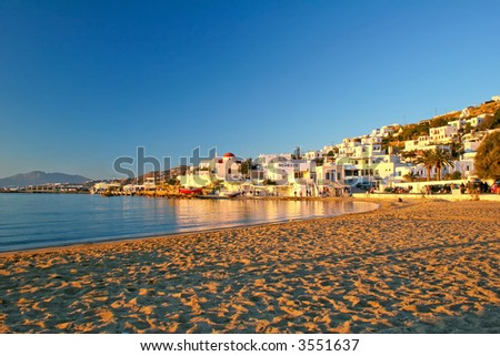 Mykonos Beach at sunset detailing the white wash buildings - stock photo