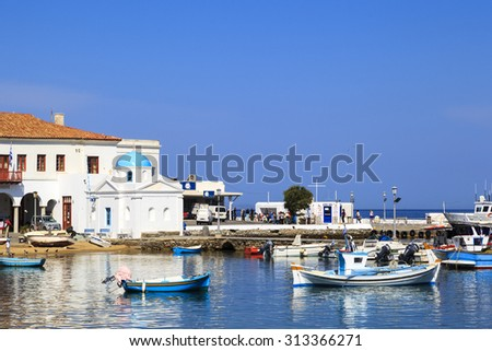 MYKONOS, GREECE- MAY 24 2014: Port of Mykonos whitewashed and blue domed Agios Nikolaos church on island Mykonos, Greece.  The island spans an area of 85.5 square kilometers. - stock photo