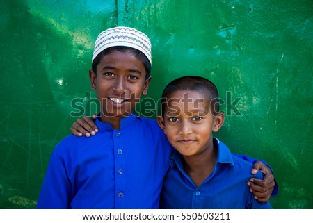 MYMENSINGH, BANGLADESH - JANUARY 2, 2017: Two young boys wearing a blue shirt and one with a kufi in front of a green gate