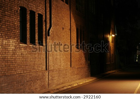Mysterious Alley - Dark Abandoned Street With Lights Shining On A Brick Wall - stock photo