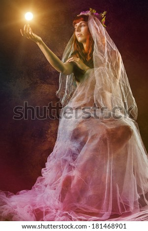 Mysterious and sensual girl with a transparent cloth holding a little sun.