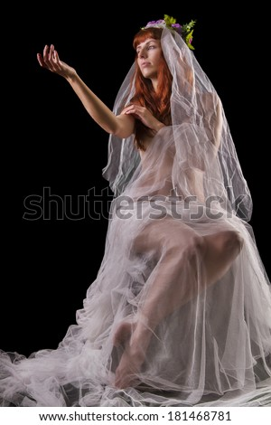 Mysterious and sensual girl with a transparent cloth with a crown of flowers isolated on a black background.