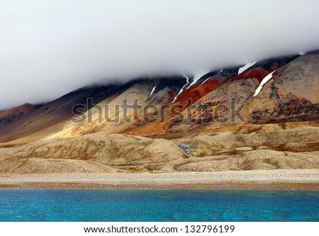 Mysterious arctic view - bright blue waters of Recherchefjorden and barren shore with melting snow and heavy fog, Spitsbergen (Svalbard island), Norway, Greenland Sea, Atlantic ocean - stock photo