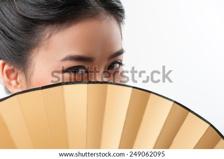 Mysterious Asian beauty. Attractive asian woman wearing Japanese kimono hiding behind traditional fan while standing isolated against white background with copy space - stock photo